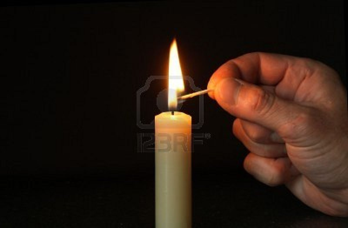 Hand Lighting Match And Candle In Dark New Earth Uk